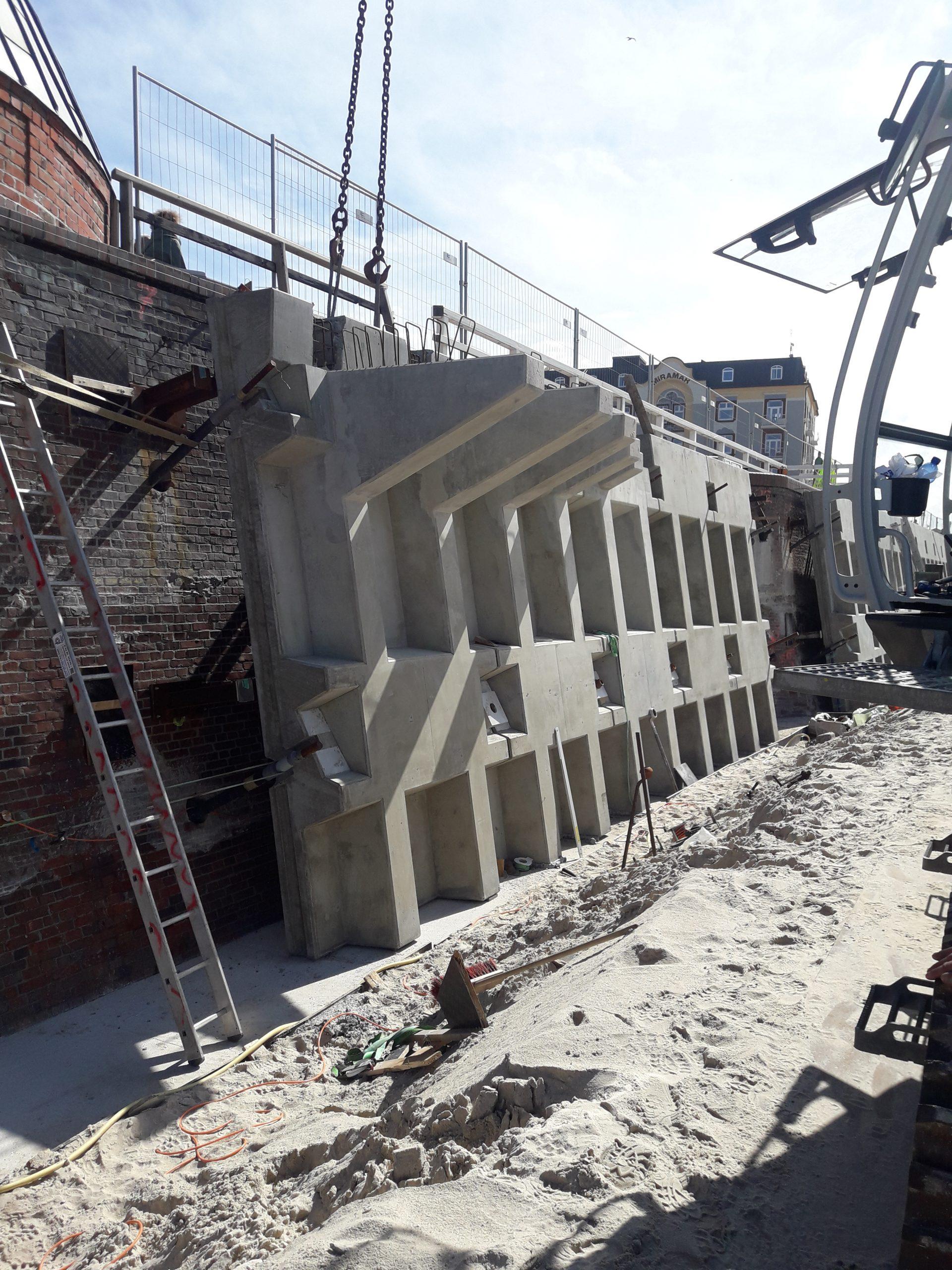 Die ersten Wandteile werden an Ort und Stelle gebracht